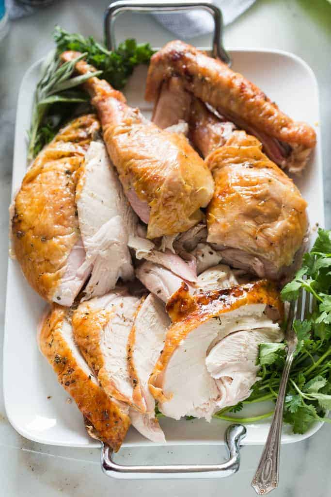 White and dark meat carved from a turkey, served on a large white platter with fresh green herbs.