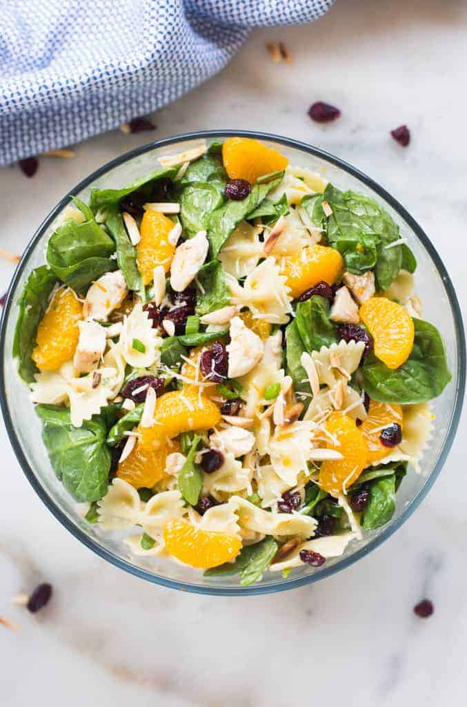 Spinach, chicken, crainsin, mandarin oranges, and slivered almonds in a glass bowl.