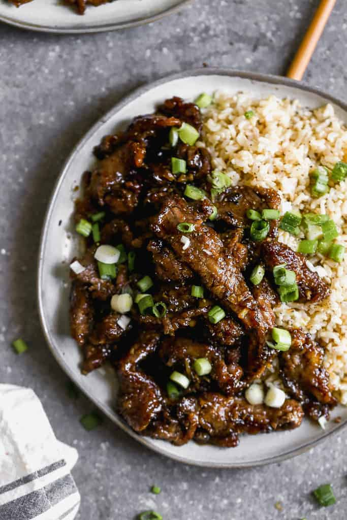 A plate with Mongolian beef, brown rice and chopsticks on the side.