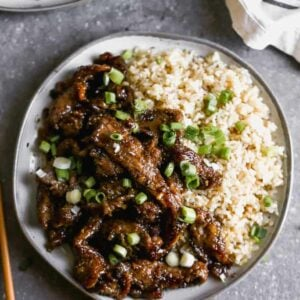 Mongolian beef on a plate with rice and chopped green onion on top.