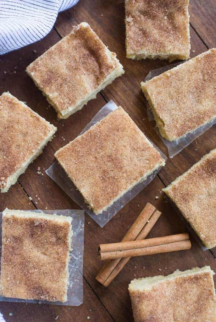 Several square snickerdoodle bars on small pieces of wax paper on a wooden table.