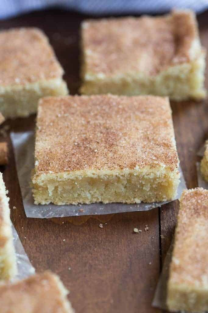 A close up image of a chewy snickerdoodle bar on a wooden table.