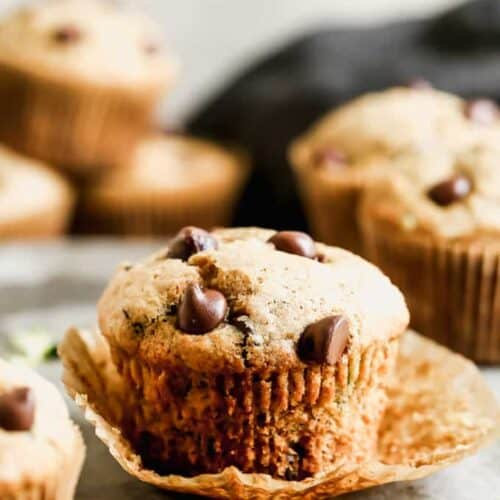A zucchini muffin with its paper liner peeled down, surrounded by more muffins.