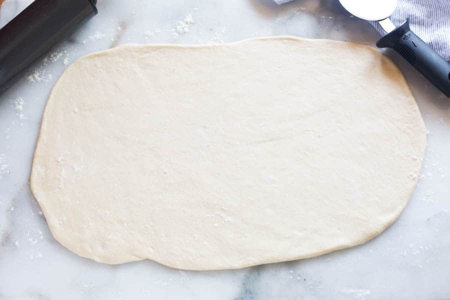 Bread dough rolled out into a long rectangle, with a rolling pin to the side.