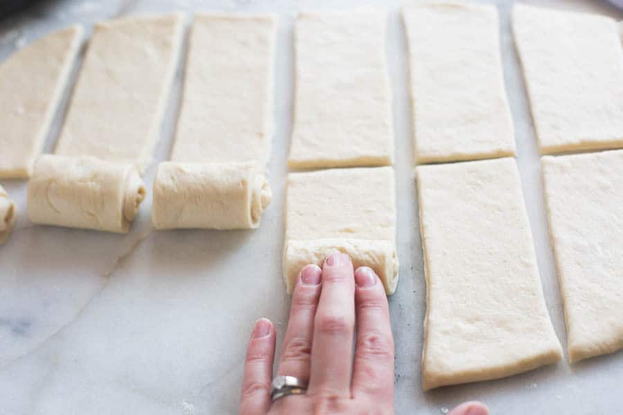 Bread dough rolled out and cut into 12 small rectangles, with the fingers of a hand rolling the dough up.