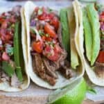 Three carne asada tacos in a line with pico de gallo and avocados.