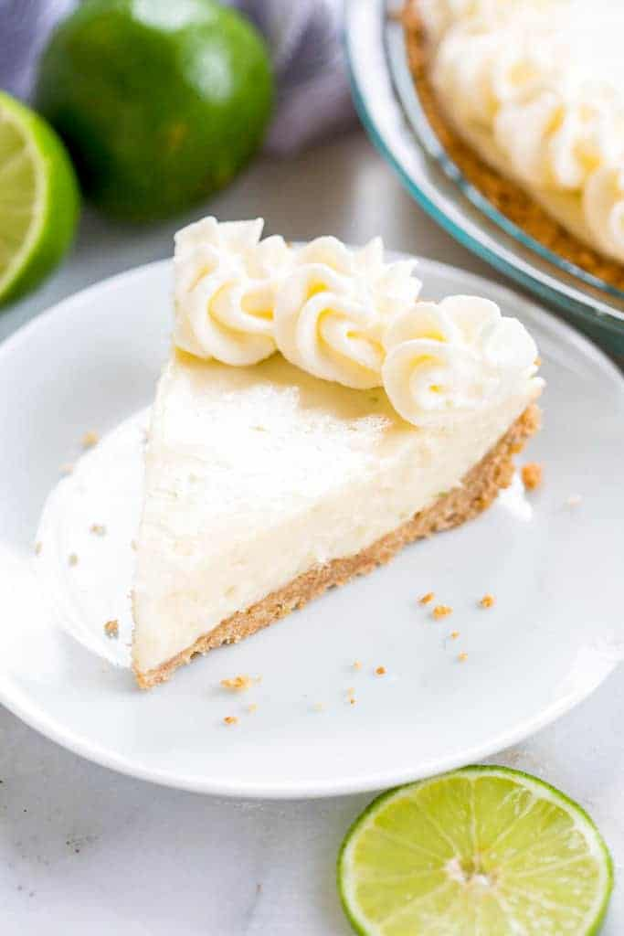 A slice of key lime pie on a white plate with limes and the pie dish in the background.