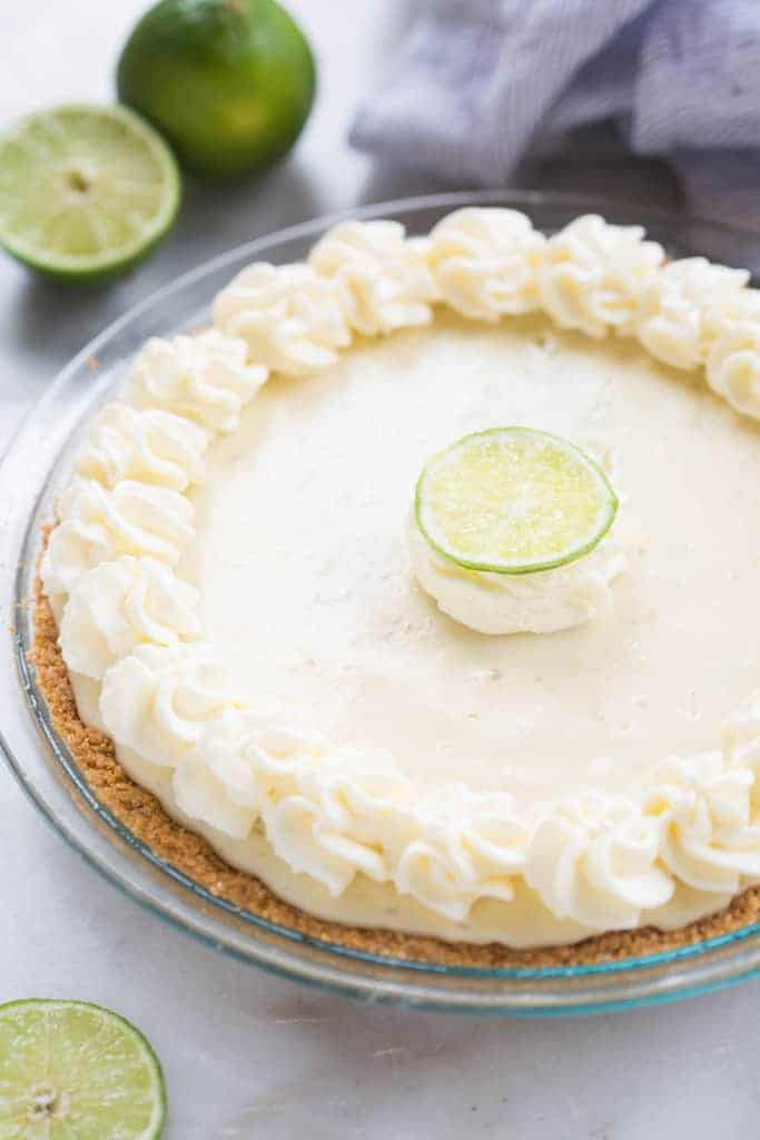 A close up of a key lime pie in a glass dish with piped flowers of whipped cream around the edges.