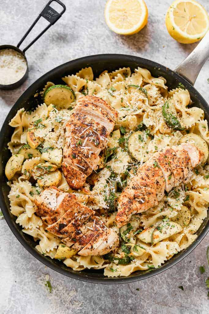 A skillet with warm lemon chicken pasta in it, ready to serve.