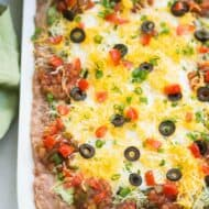 Everyone loves this easy 7-layer bean dip that has layers of flavored refried beans, guacamole, sour cream, salsa, cheese, olives and green onion. | tastesbetterfromscratch.com