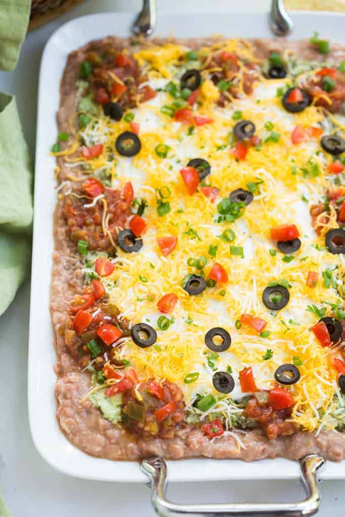 7-layer bean dip with refried beans, guacamole, sour cream, salsa, cheese, olives and green onion on a white serving tray.