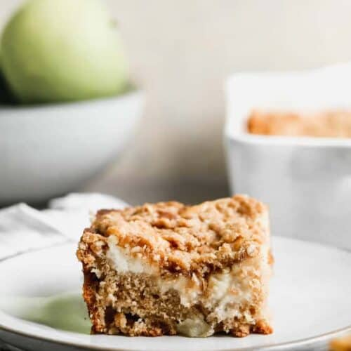 A slice of Apple Coffee Cake on a white plate with the cake pan and a bowl of apples in the backround.