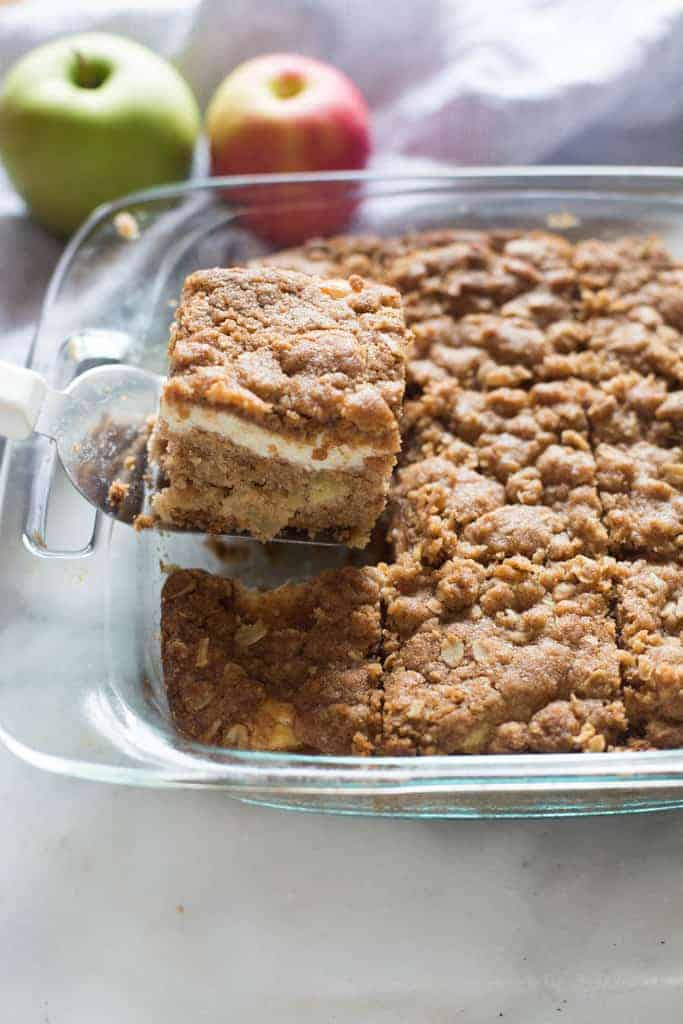 A slice of Apple Coffee Cake with cream cheese filling being removed from a glass baking dish.