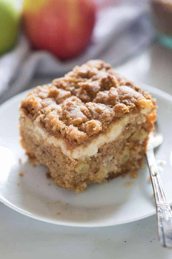 A slice of Apple Coffee Cake with cream cheese filling and a streusel topping on a white plate with a fork.