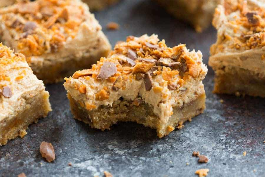 Take a big bite out of these Butterfinger Cookie Bars with butterfinger frosting. | tastesbetterfromscratch.com