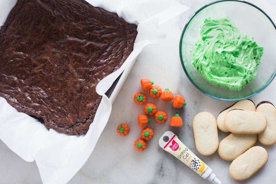 A pan of brownies that have been emptied onto parchment paper, a clear dish with green frosting, several pumpkin candy corns, and milano cookies