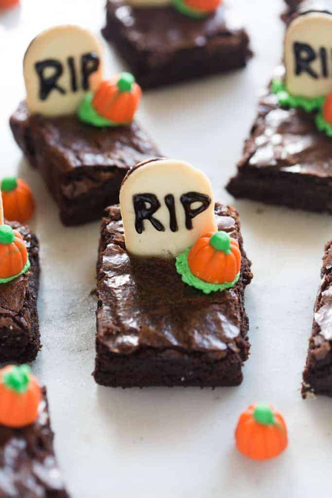 Several brownies cut into rectangles with half a Milano cookies sticking out (with the words RIP written on it) and a pumpkin candy corn.