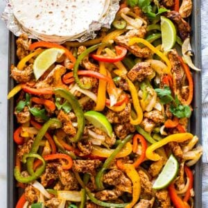 A sheet pan with cooked chicken and bell peppers seasoned for fajitas.