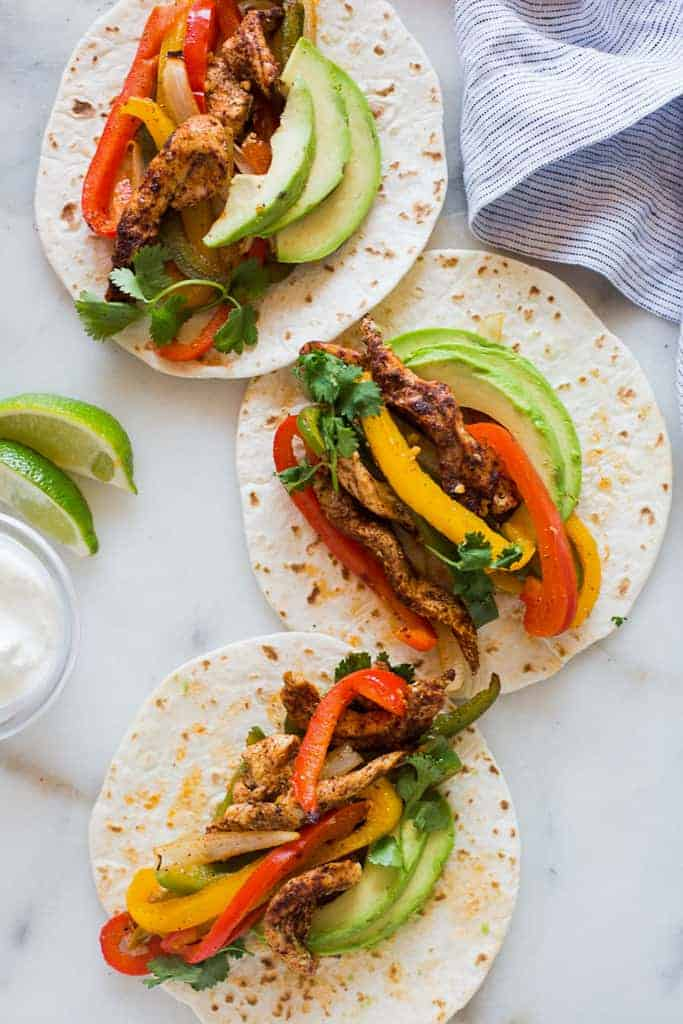 Three flour tortillas topped with fajita chicken and vegetables.