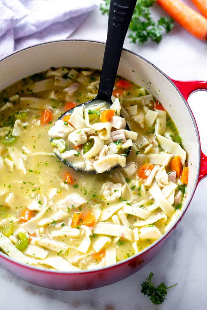 A ladle full of homemade chicken noodle soup lifting if from the soup pot.