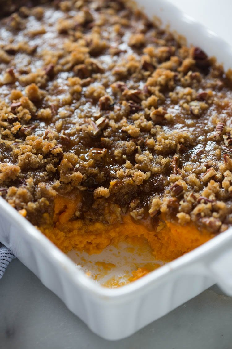 The front corner of a casserole dish willed with sweet potato casserole with brown sugar pecan topping and a bite missing.
