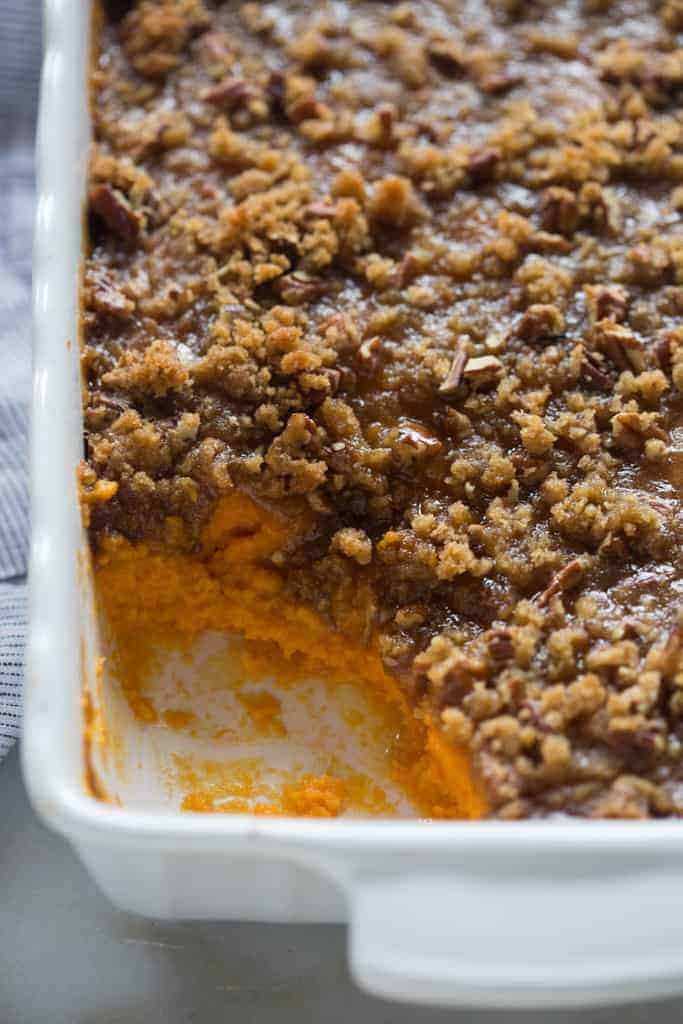 One large scoop missing from the front corner of a sweet potato casserole dish.