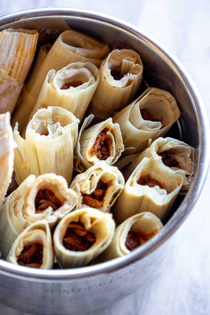 Pork tamales stacked in a pot.