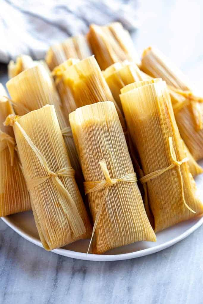 Tamales wrapped in corn husks and tied, lined up on a plate.