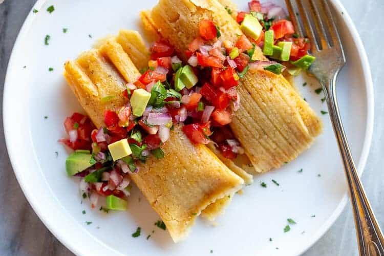 Two tamales on a plate with pico de gallo and chopped avocado.