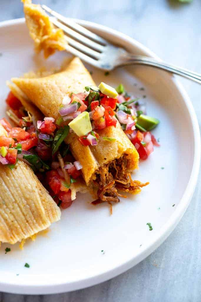 Tamale with pork filling, pico de gallo on top and a fork taken a bite out of it.