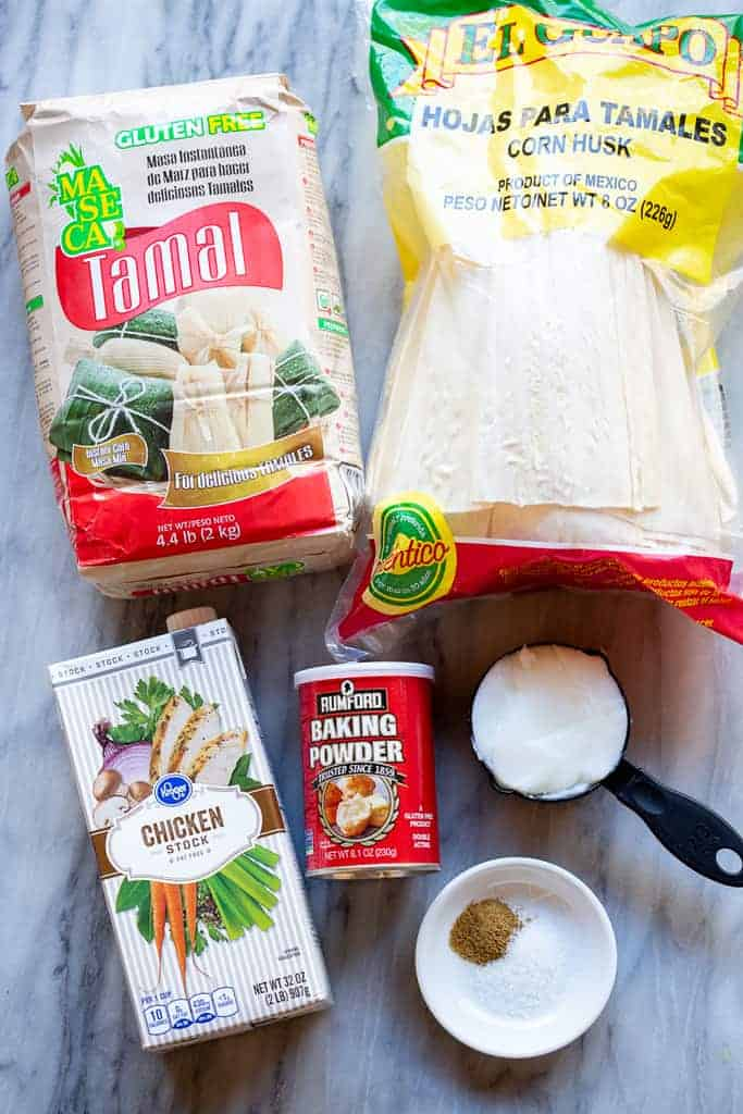 Ingredients for tamales including masa harina, corn husks, lard, broth, baking powder and spices.
