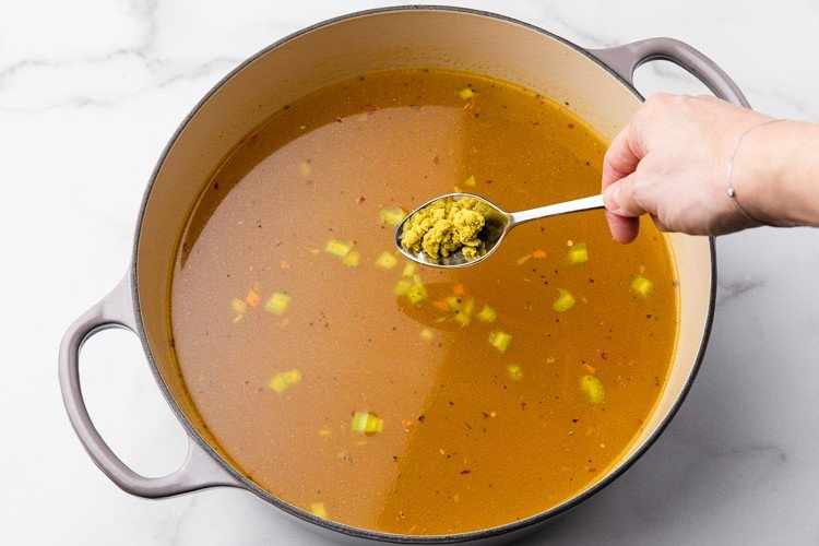 Chicken stock spices and bullion added to a pot to make chicken noodle soup.
