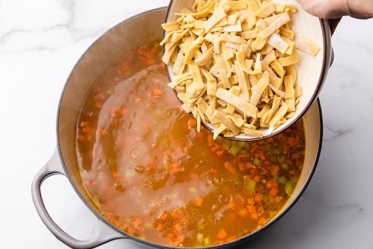 Homemade egg noodles being added to a pot of chicken stock and veggies.