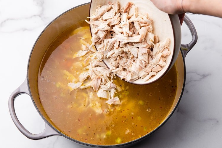 Rotisserie chicken being added to a large soup pot of chicken noodle soup.
