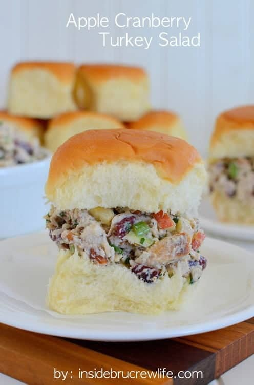 A hawaiian roll filled with apple cranberry turkey salad on a white plate. Several more sandwiches are visible in the background.