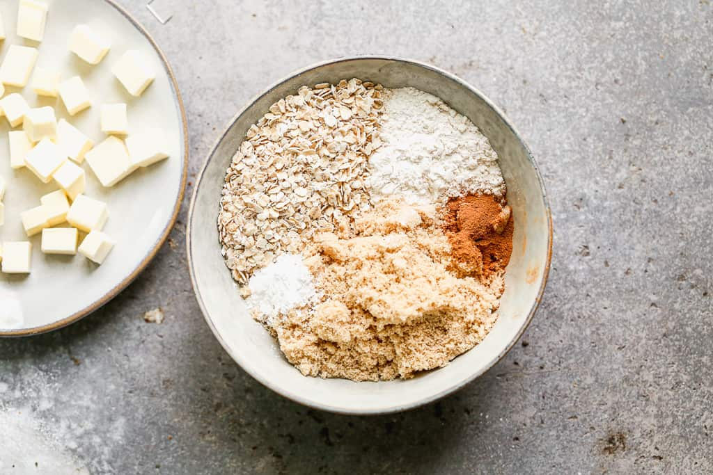 Oats, flour, cinnamon brown sugar and cubed butter in a bowl to make cumb topping for apple crisp.