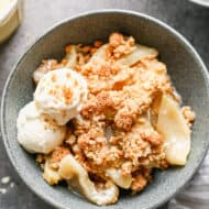 Apple Crisp served in a bowl with a scoop of vanilla ice cream on the side.