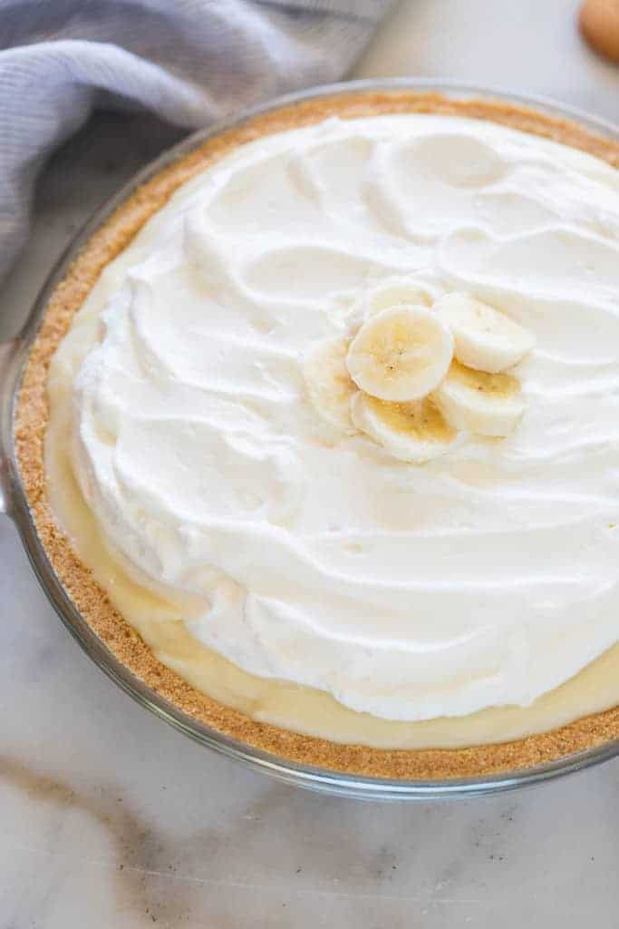 Banana Cream Pie in a clear pie dish with a dish towel and nilla wafers in the background