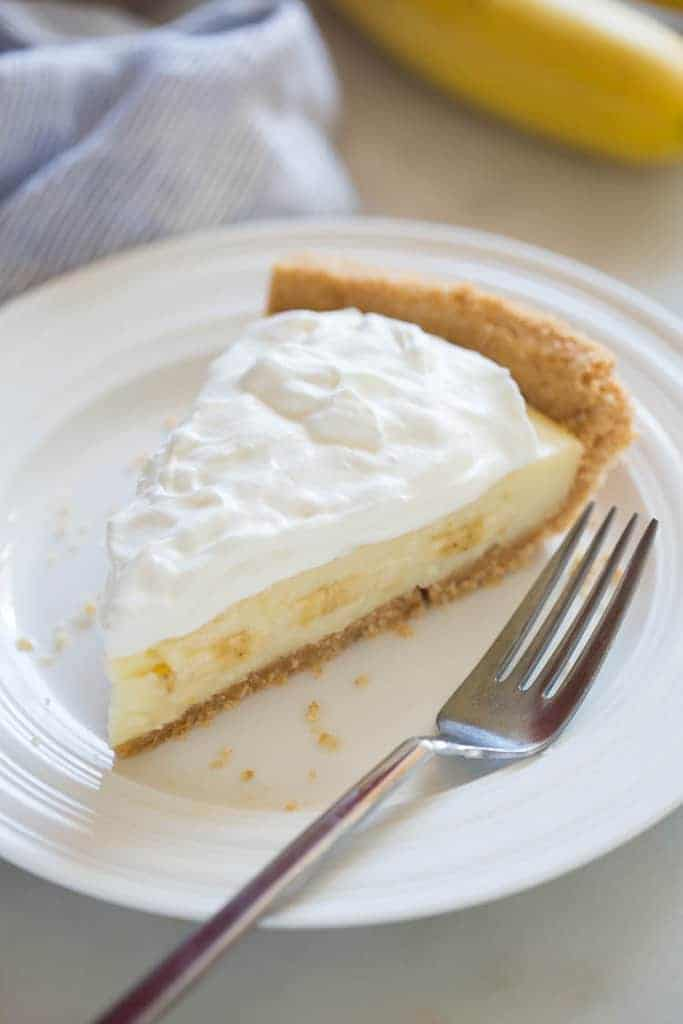 A slice of Banana Cream Pie with nilla wafer crust on a white plate with a fork, a napkin and banana in the background.