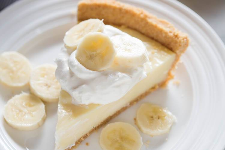 Banana Cream Pie slice on a white plate with fresh banana slices on top of whipped cream.