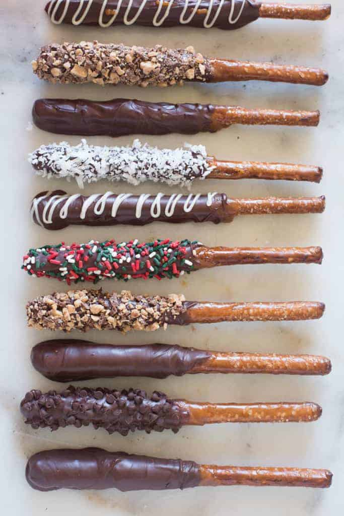 Ten pretzel rods laying horizontally in a row, dipped in caramel and chocolate and sprinkled with various toppings.
