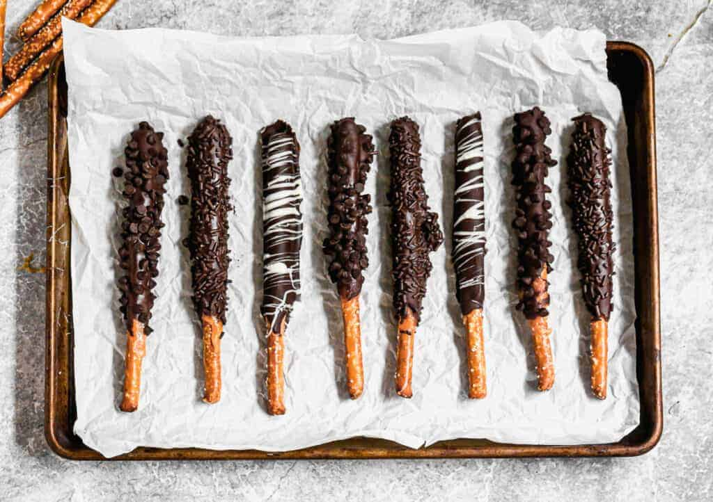 Chocolate dipped pretzel rods lined on a baking sheet, topped with mini chocolate chips, sprinkles, or a drizzle of white chocolate..
