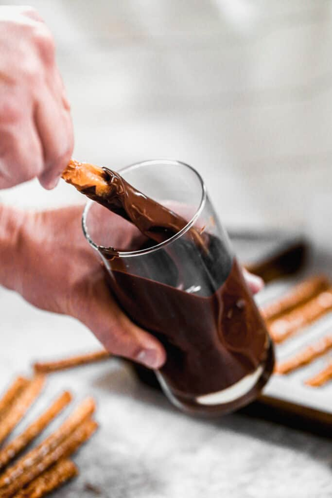 A hand dipping a pretzel rod in a cup of melted chocolate.