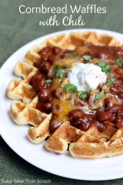 A white plate with a cornbread waffle covered with chili, cheese, and topped with sour cream