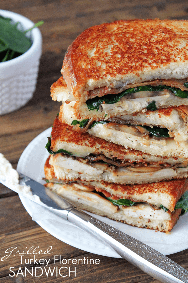 Four halves of grilled turkey florentine sandwiches stacked on a white plate.