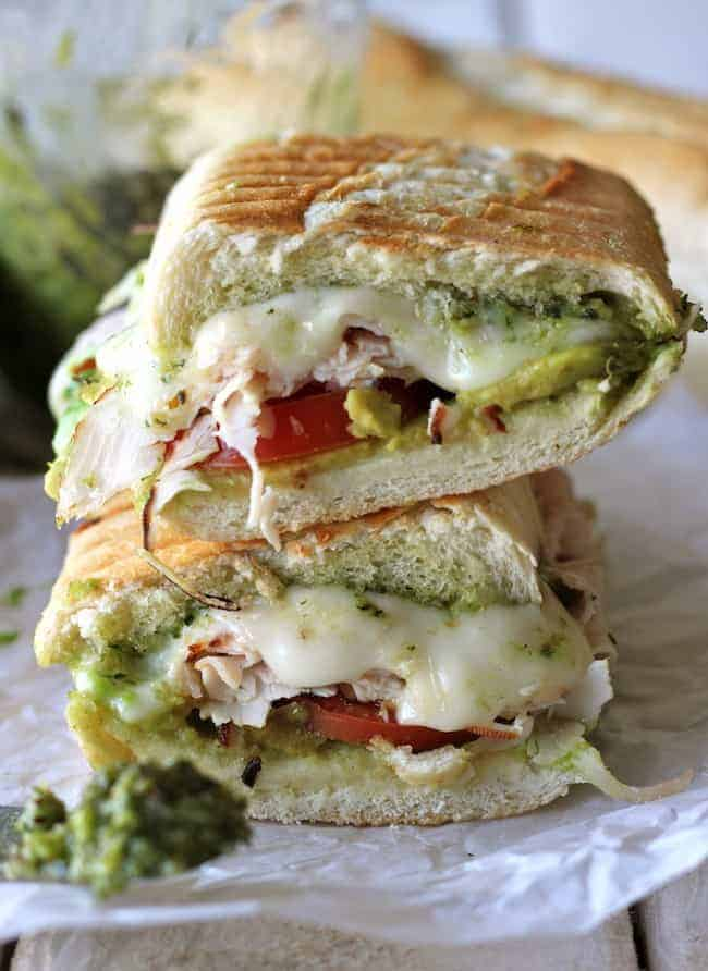 Two halves of a turkey pesto panini stacked on parchment.