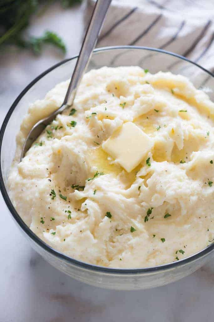 A bowl of creamy mashed potatoes with a slice of butter, and a large serving spoon.