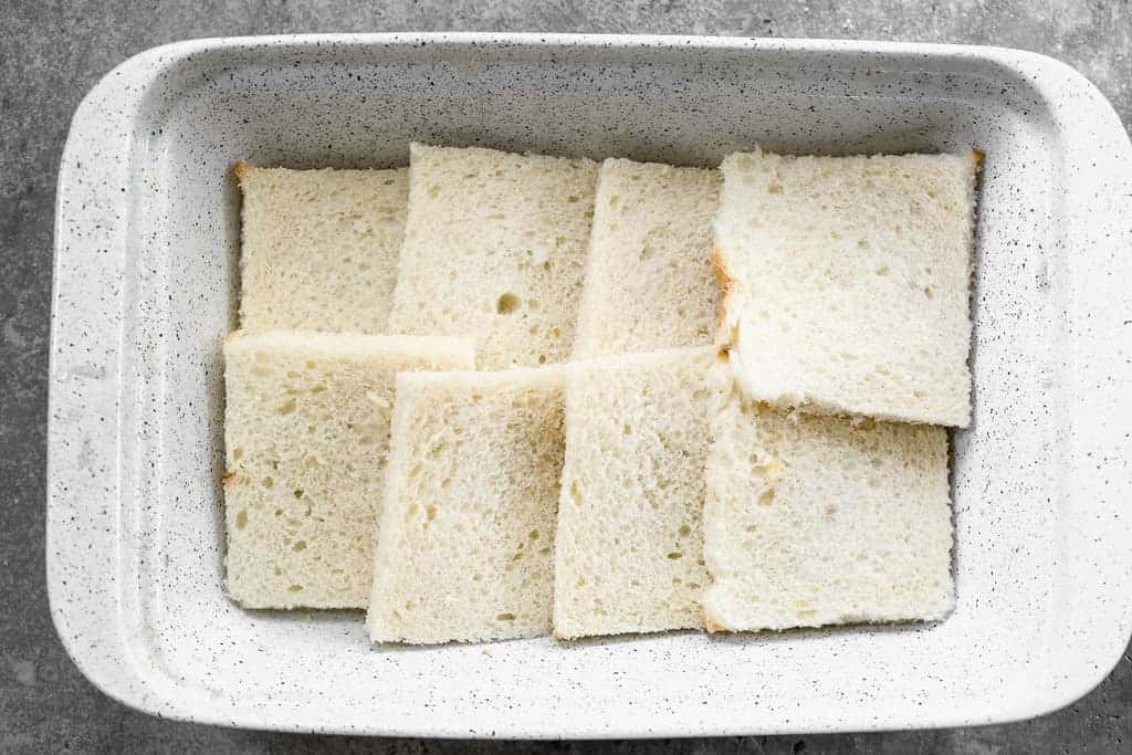 A casserole dish with slices of white bread laid along the bottom.