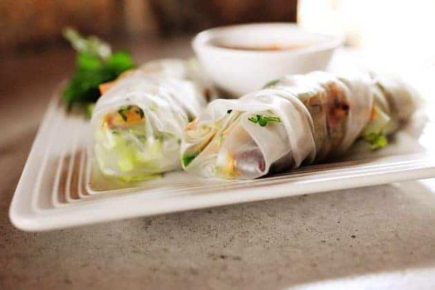 A textured white plate with two leftover turkey spring rolls along with a small white bowl containing sauce.