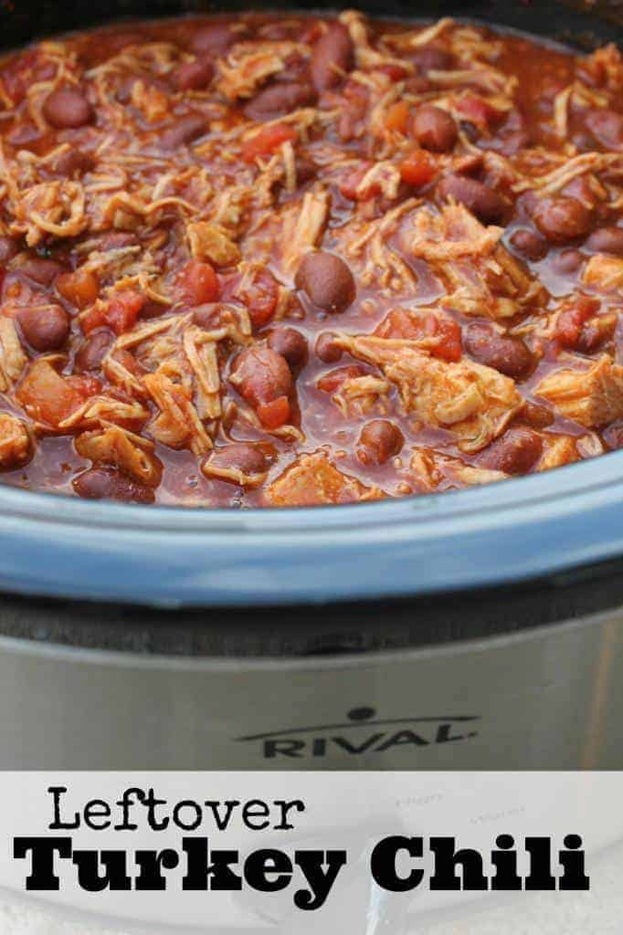 A crockpot with a blue rim full of leftover turkey chili.